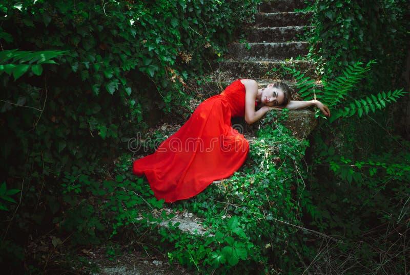 Красивая женщина в красном платье лежа на шагах старой лестницы стоковое изображение