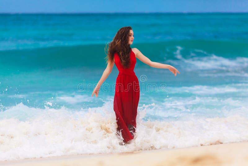 Красивая женщина в красном платье на тропическом морском побережье стоковые изображения rf
