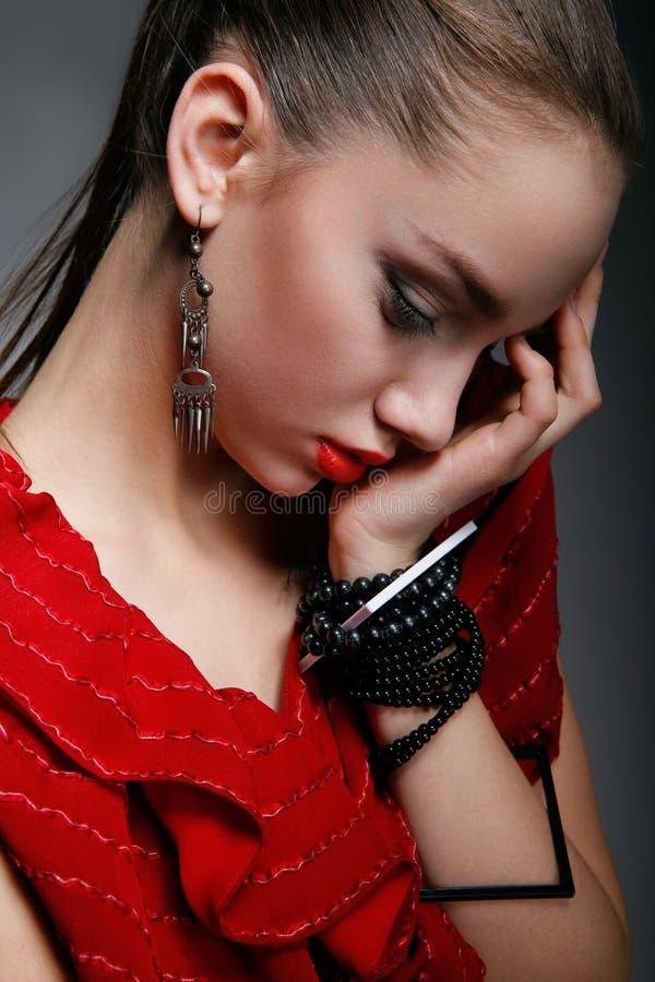 Красивая женщина в красном платье с закрытыми глазами стоковое фото rf
