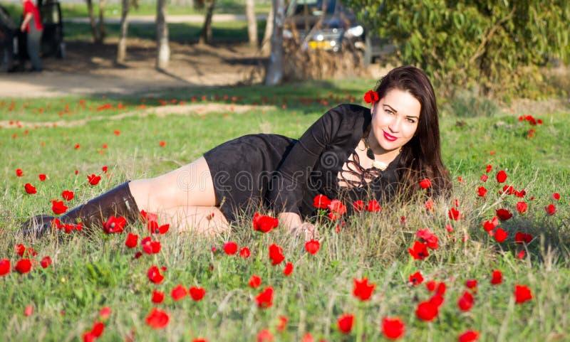 Красивая женщина в красных цветках стоковые изображения