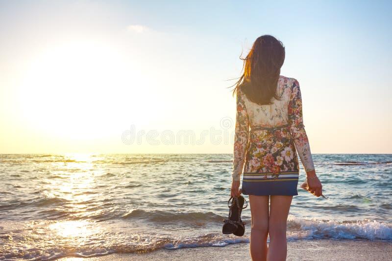 Красивая женщина в красочном платье стоя на пляже около океана и смотря далеко на заходе солнца стоковые изображения
