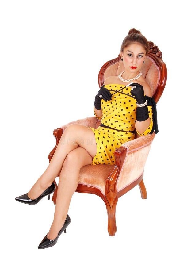 Красивая женщина в кресле с сигаретой стоковое фото