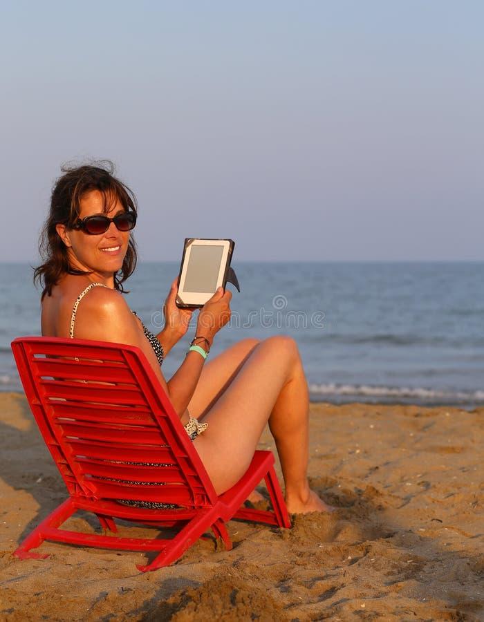 Красивая женщина в купальнике читает ebook на пляже стоковое фото rf