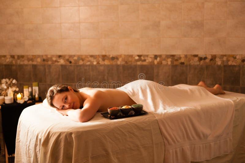 Красивая женщина в курорте ослабляя на плате массажа стоковые фото