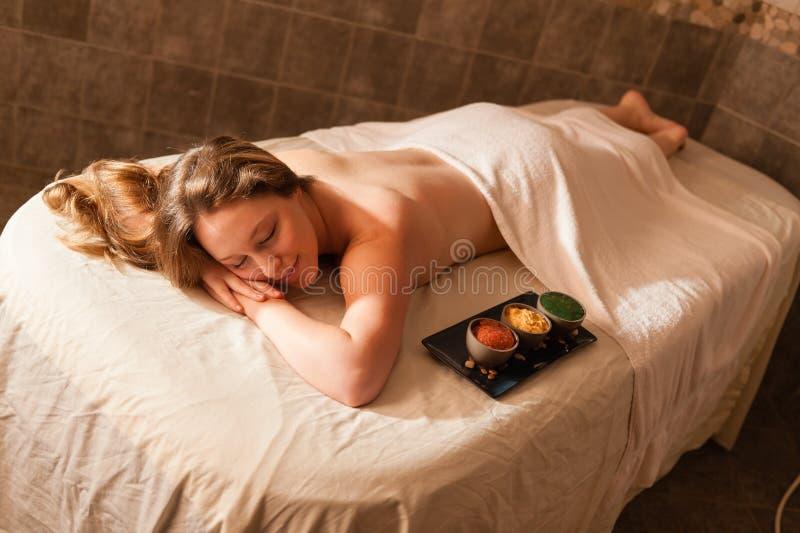 Красивая женщина в курорте ослабляя на таблице массажа. стоковое изображение