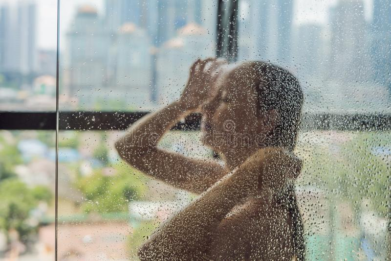 Красивая женщина в ливне за стеклом с падениями на bac стоковые фотографии rf