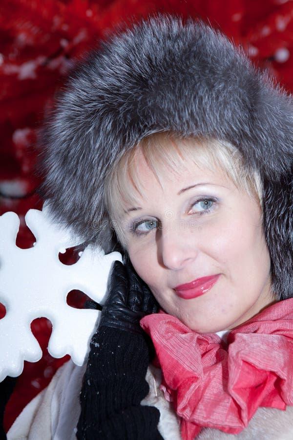 Красивая женщина в меховой шапке зимы на красной рождественской елке предпосылки стоковые фото