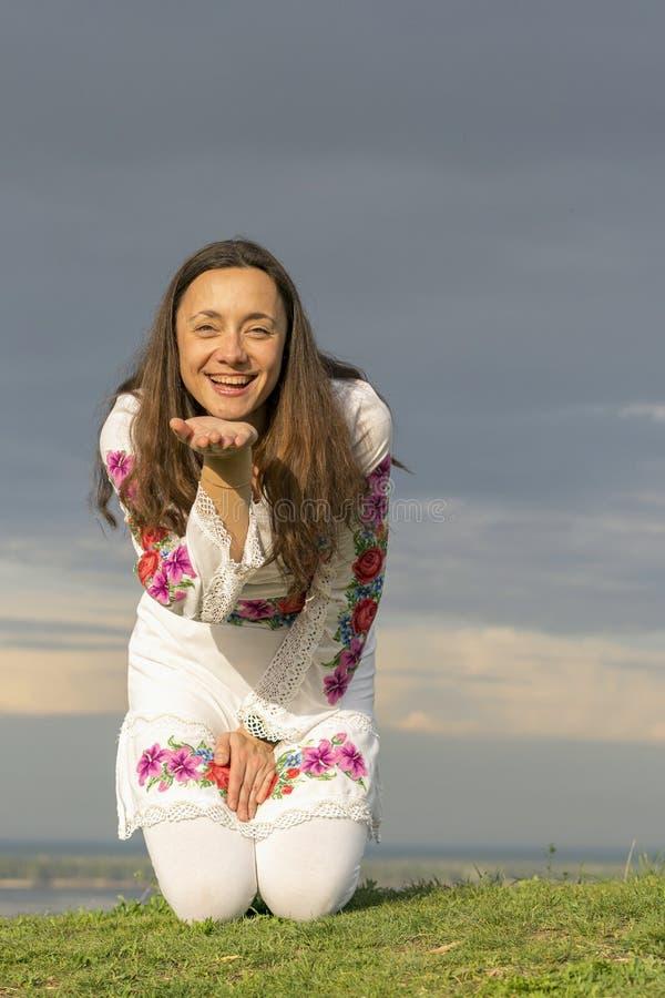 Красивая женщина в модных одеждах на предпосылке драматического неба Сексуальная женщина в национальных одеждах ( стоковое изображение rf