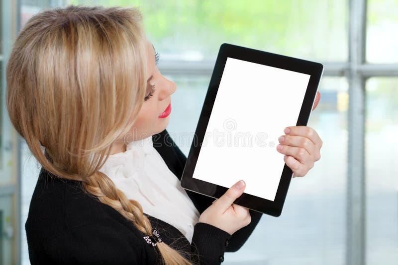 Красивая женщина в офисе держа таблетку с изолированным scr стоковое фото rf