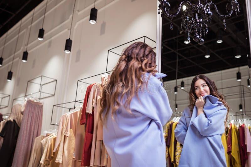 Красивая женщина в пальто в магазине стоковое фото rf