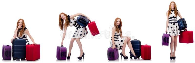 Красивая женщина в платье точки польки с чемоданами изолированными на белизне стоковые изображения