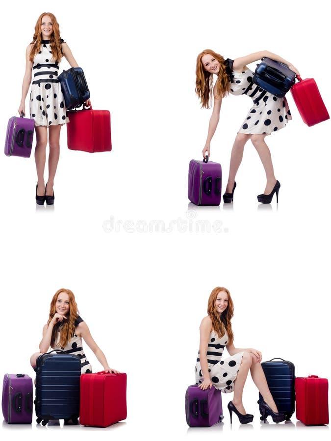 Красивая женщина в платье точки польки с чемоданами изолированными на белизне стоковое фото