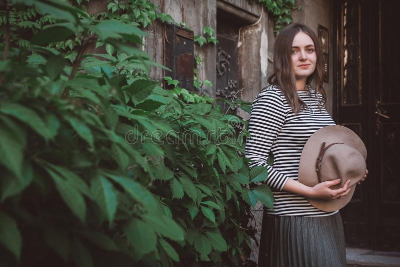Красивая женщина в полосатой рубашке, держащая шляпу и глядя на камеру, стоковые фотографии rf