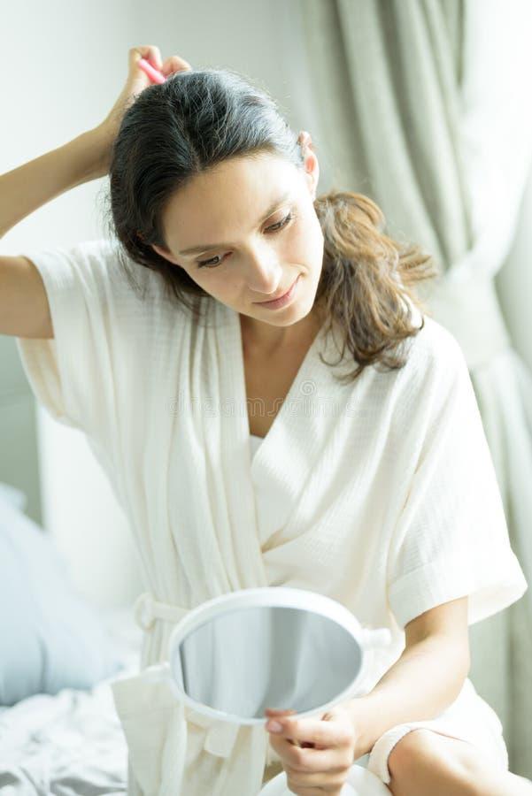 Красивая женщина в полотенце и белом халате должна выглядеть в зеркале для расчесывания волос с розовым комбом и на кровати у кро стоковые изображения
