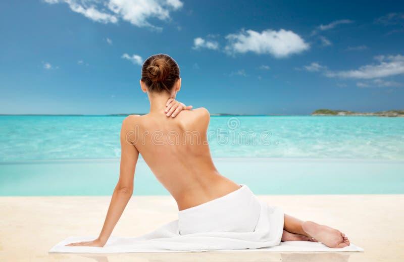 Красивая женщина в полотенце с чуть-чуть верхней частью на пляже стоковая фотография