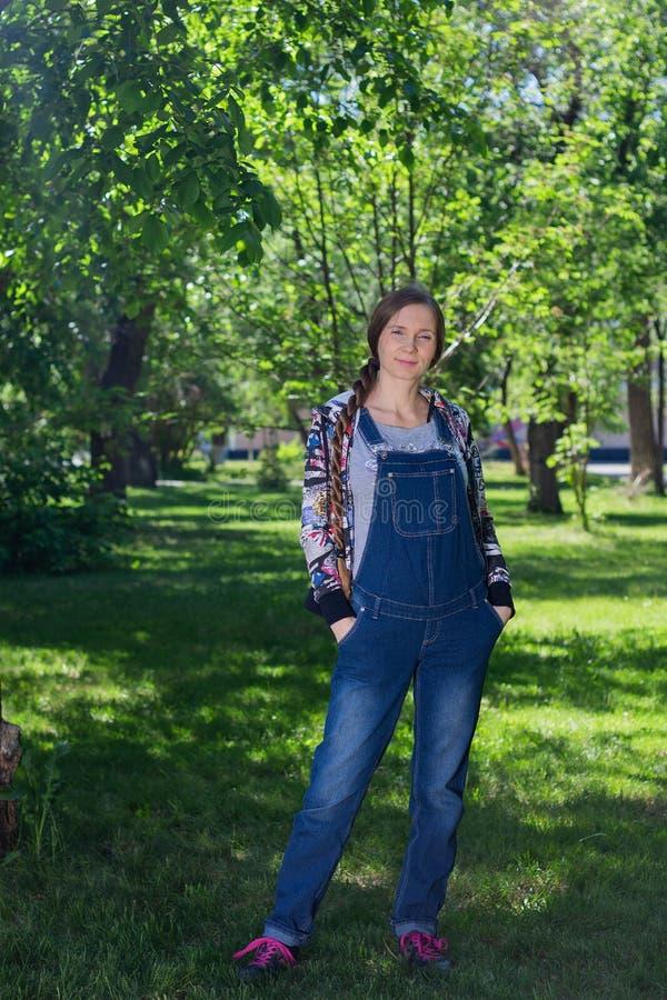 красивая женщина в предыдущей беременности в комбинезоне джинсовой ткани, стоя на зеленой траве в парке стоковые изображения rf