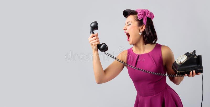 Красивая женщина в пурпурном платье с винтажным черным телефоном стоковое фото