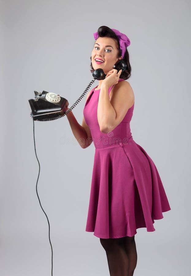 Красивая женщина в пурпурном платье с винтажным черным телефоном стоковое фото rf
