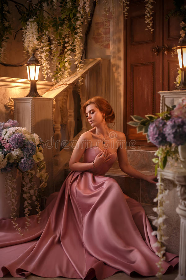 Красивая женщина в роскошном розовом платье стоковое изображение