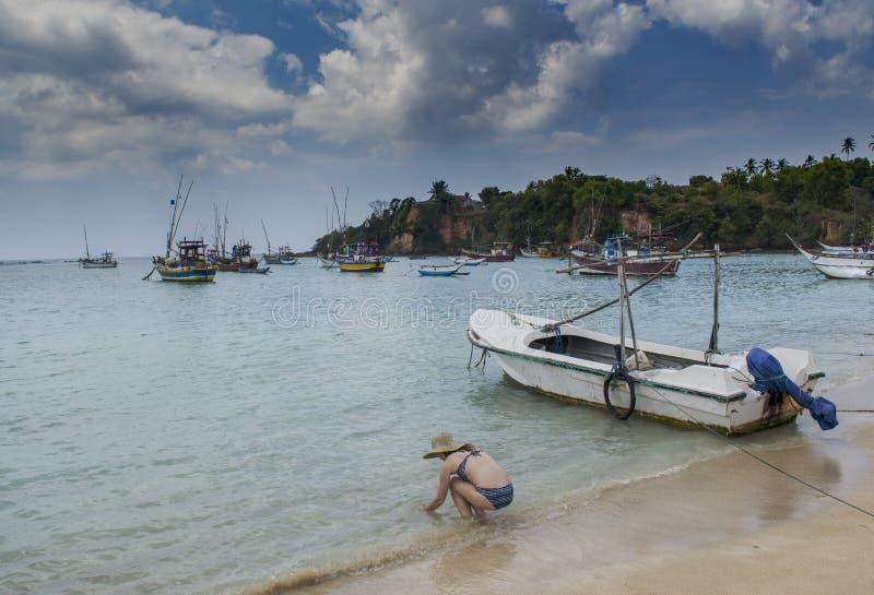 Красивая женщина в руках шляпы моя в океане на гавани стоковая фотография rf