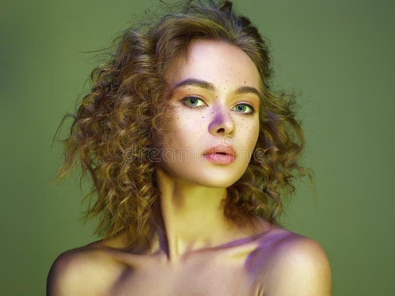 Красивая женщина в свете цвета изумляя курчавая девушка стоковые фото