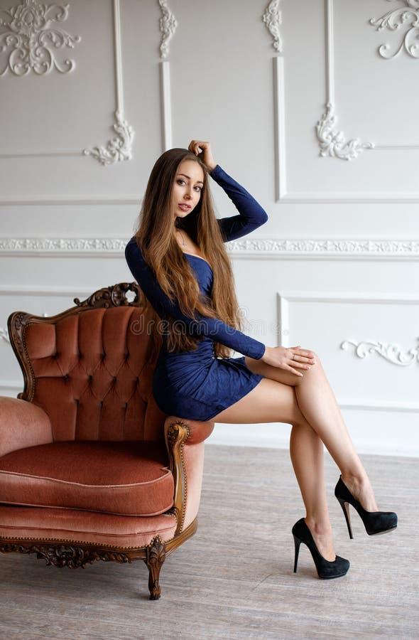 Красивая женщина в сексуальном коротком платье на софе стоковое изображение rf