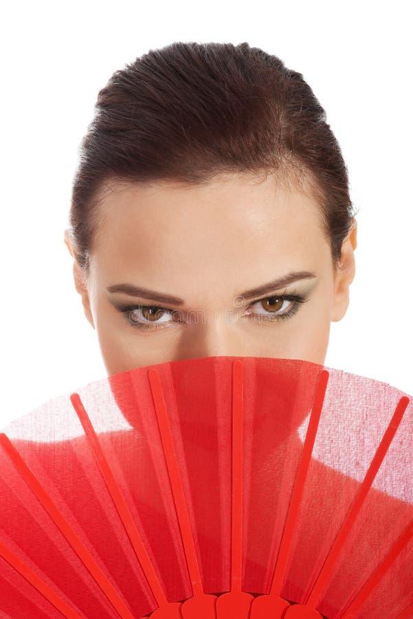 Красивая женщина в сексуальном красном платье с вентилятором. стоковая фотография