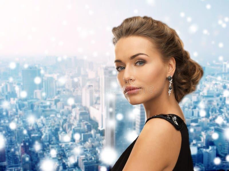 Красивая женщина в серьгах платья вечера нося стоковое изображение rf