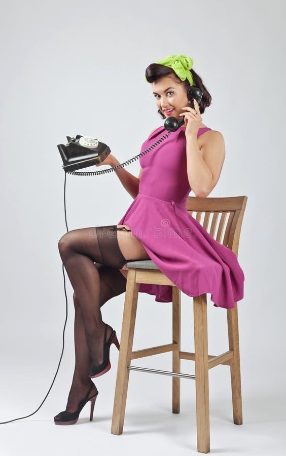 Красивая женщина в стиле штыря поднимающем вверх с винтажным телефоном стоковое фото rf