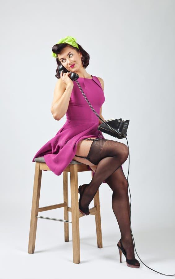 Красивая женщина в стиле штыря поднимающем вверх с винтажным телефоном стоковая фотография rf