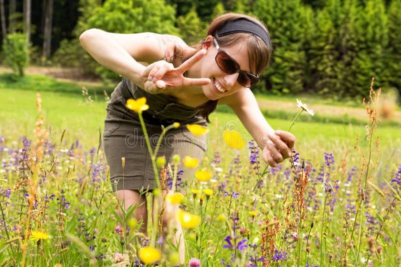 Красивая женщина в луге wildflower показывает символ победы стоковое фото rf