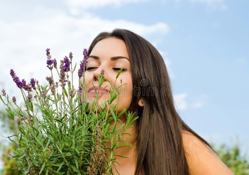 Красивая женщина в цветках сада пахнуть. стоковое изображение