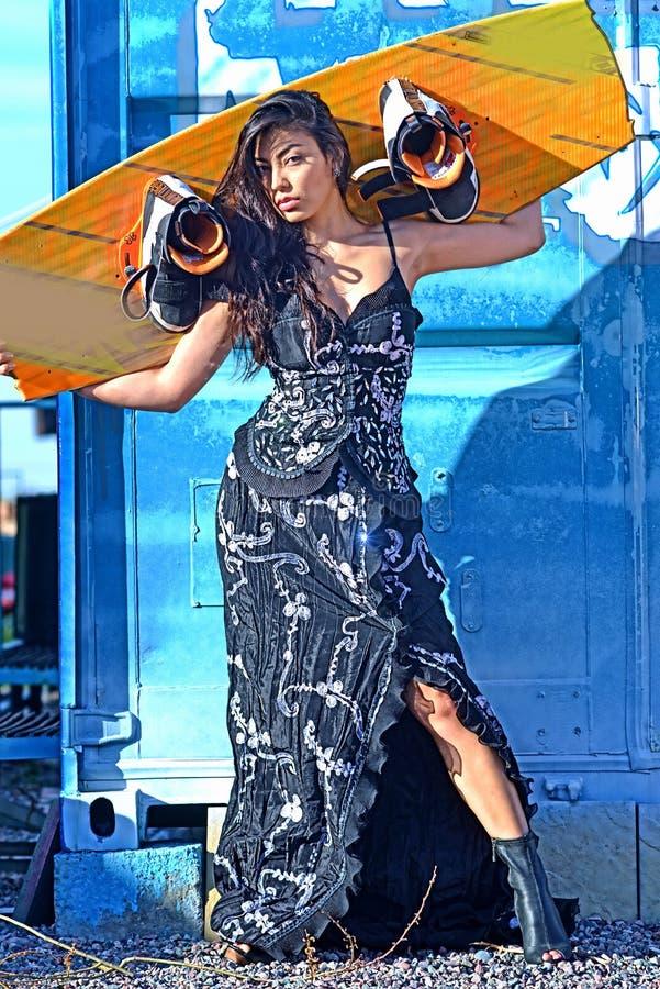 Красивая женщина в черном белом платье, длинных волосах стоя с wakeboad на утюге сини bacground, граффити стоковые изображения