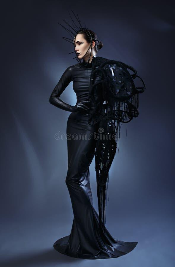 Красивая женщина в черном готическом платье Сторона нося маску стоковое фото rf