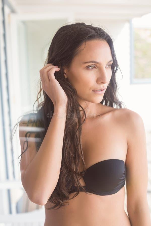 Красивая женщина в черный представлять бикини стоковое фото