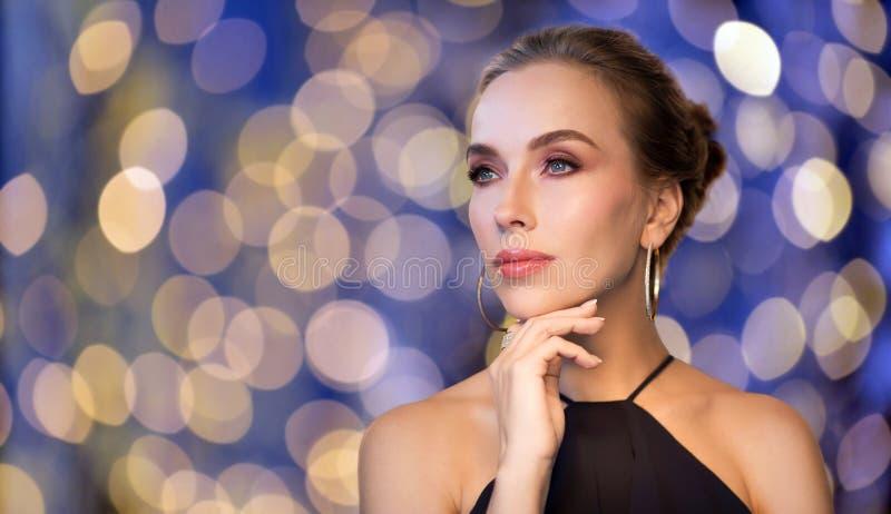 Красивая женщина в черных нося ювелирных изделиях диаманта стоковое изображение rf