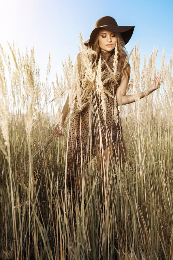 Красивая женщина в шляпе в луге tallgrass на золотом часе стоковая фотография