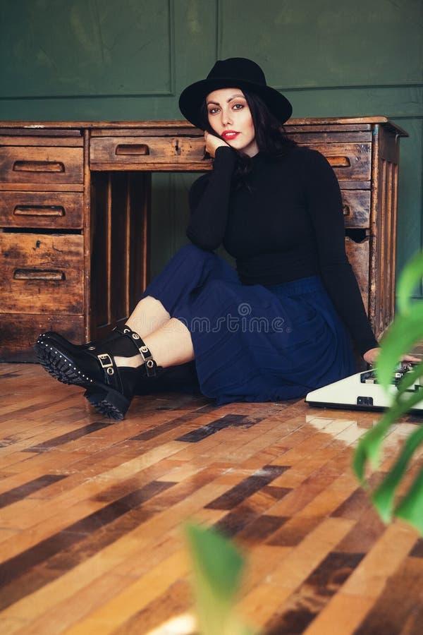 Красивая женщина в шляпе сидит около таблицы дуба с винтажной машинкой стоковые фото