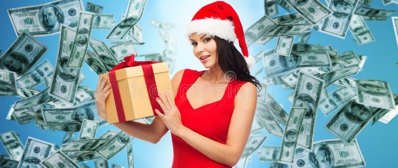 Красивая женщина в шляпе santa с подарком над деньгами стоковое фото rf