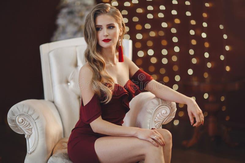 Красивая женщина в элегантном внешнем платье представляя самостоятельно, сидящ в стуле стоковая фотография rf