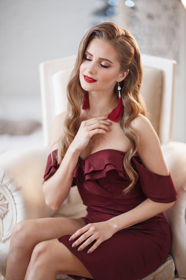 Красивая женщина в элегантном внешнем платье представляя самостоятельно, сидящ в стуле стоковые фотографии rf