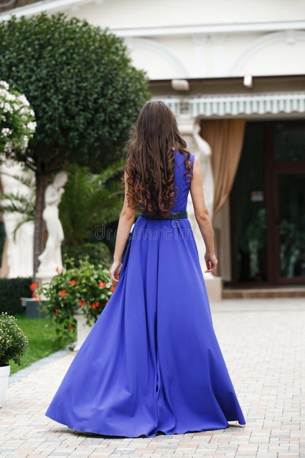 Красивая женщина в элегантном голубом платье вечера задний взгляд стоковая фотография