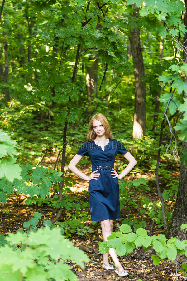 Красивая женщина в элегантном платье и очаровательной улыбке представляя в парке Девушка дела идет после работы стоковое фото
