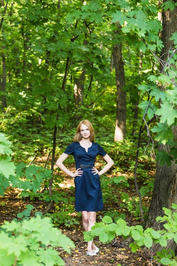 Красивая женщина в элегантном платье и очаровательной улыбке представляя в парке Девушка дела идет после работы стоковое изображение