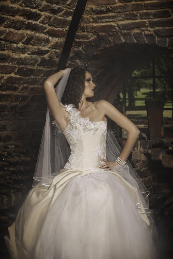 Красивая женщина в cream и белом платье свадьбы стоковая фотография