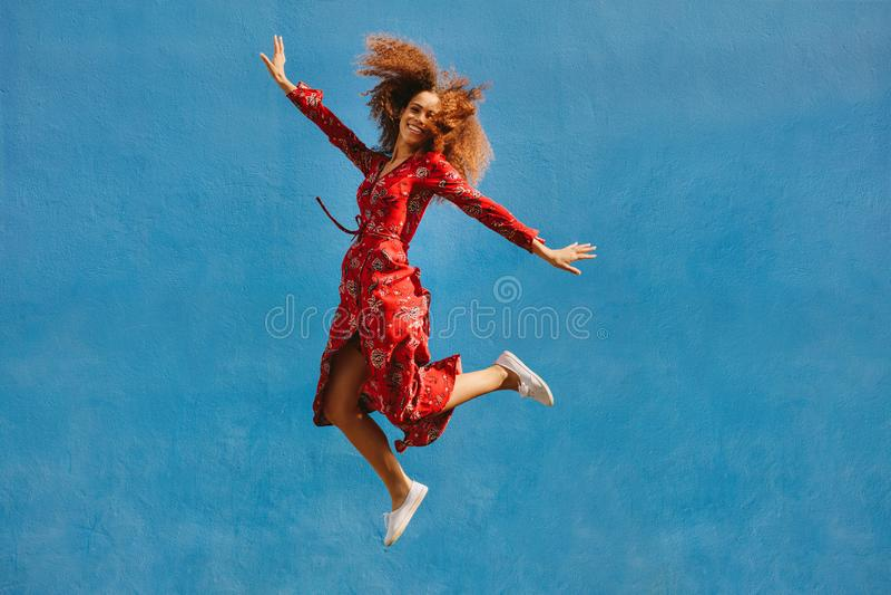 Красивая женщина в sundress скача с утехой стоковое фото