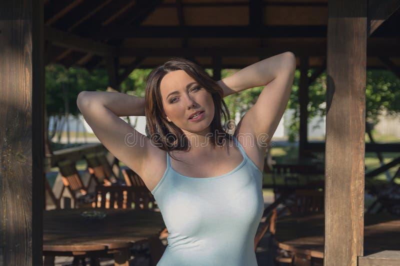 Красивая женщина греется в солнце около газебо стоковая фотография rf