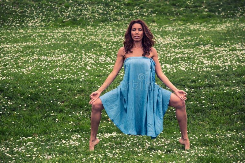 Красивая женщина делая йогу на луге стоковая фотография rf