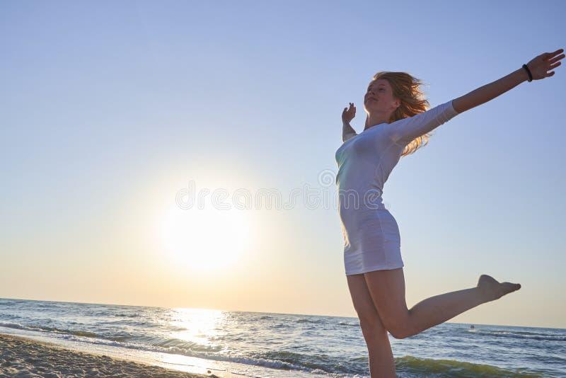 Красивая женщина делая asana йоги в пляже с defocused предпосылкой стоковое изображение