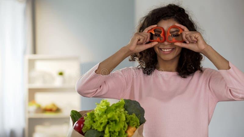 Красивая женщина держа перец звенит около глаз усмехаясь, здоровых привычек еды стоковая фотография rf